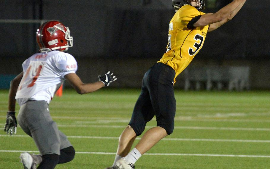 American School In Japan's Nash Rasmussen reaches for a pass as Nile C. Kinnick's Kaine Roberts gives chase.