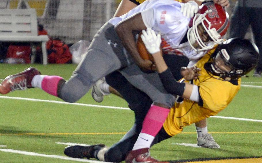 Nile C. Kinnick's Travion Morton gets dragged down by American School In Japan's Dean Hahne.