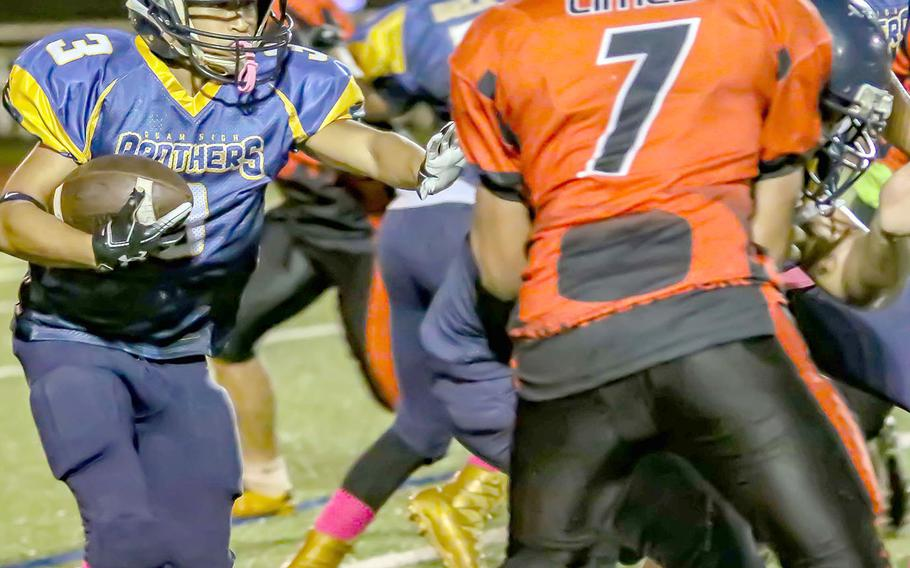 Guam High running back Julius Gaduang approaches the line and Okkodo defender Geronimo Limes.