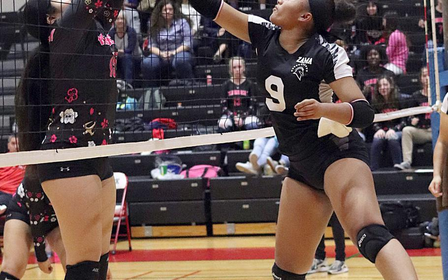 Zama's Grace Bryant and Nile C. Kinnick's Tori Osterbrink fight for the ball during Friday's five-set win by the Trojans over the Red Devils in DODEA-Japan girls volleyball tournament.