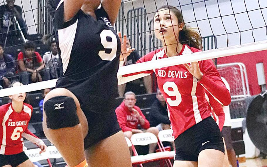 Zama's Grace Bryant plays the ball at the net against Nile C. Kinnick's Melissa Rose during Saturday's DODEA Japan girls volleyball tournament final. The Trojans rallied from one set down to beat host Nile C. Kinnick in four sets.