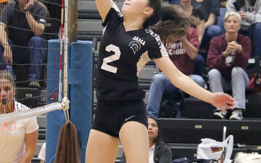 Zama's Jazlyn Rioux plays the ball at the net during Saturday's DODEA-Japan girls volleyball tournament final. The Trojans beat host Nile C. Kinnick in four sets.