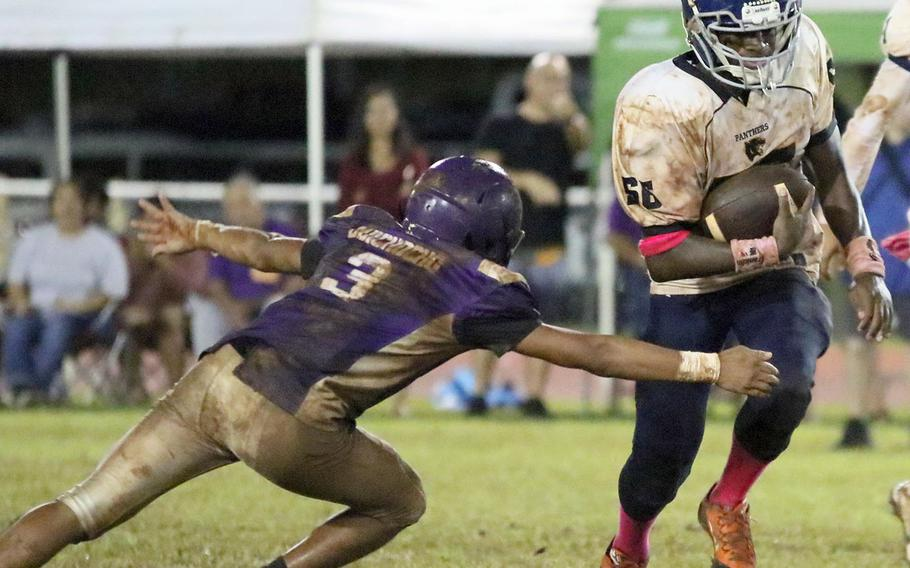 Guam High's Jeylyn Dowdell tries to avoid the tackle of George Washington's Jerome Quichocho.