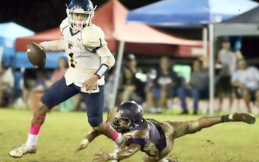 Guam HIgh quarterback Travon Jacobs eludes George Washington pressure and looks for room to run.