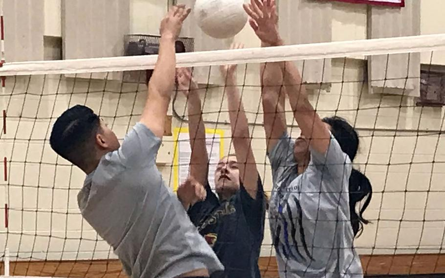 Osan spikers Maddie Taylor and Maja Inthavixay go through blocking drills with Cougars assistant coach and base team player Josh Aguirre during practice Wednesday. Osan hosts the KAIAC Plate tournament Friday and Saturday.