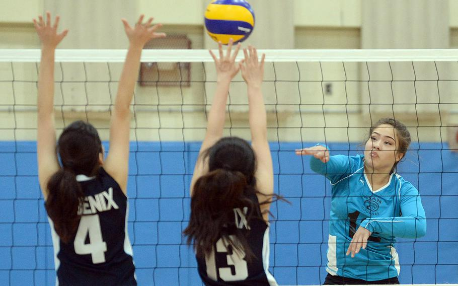 Osan's Izzy Lewis drills a spike through a Korea International School double block during Friday's five-set loss to the Phoenix on Day 1 of the Korean-American Interscholastic Activities Conference's Plate Tournament.