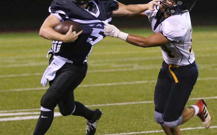 American School In Japan's Andrew Howe gets fistfuls of the jersey of Zama quarterback Nick Canada.