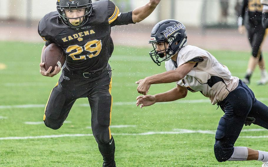 Kadena's Trent Fawler does his best to avoid being tackled by Guam High's Jalen Thach.