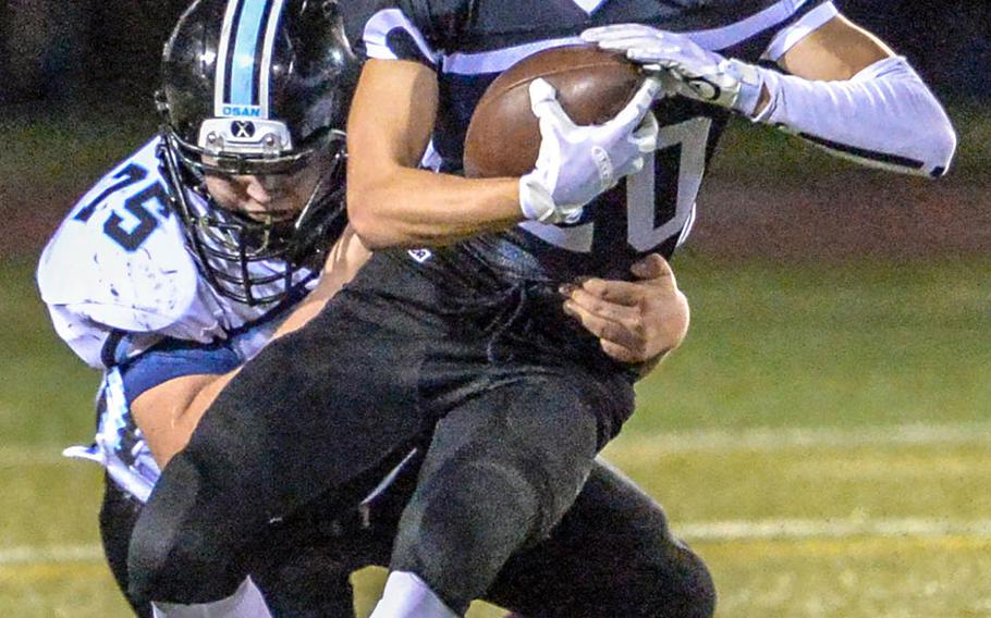 Zama running back Luke Singer gets wrapped up by Osan's Griffin Armstrong.