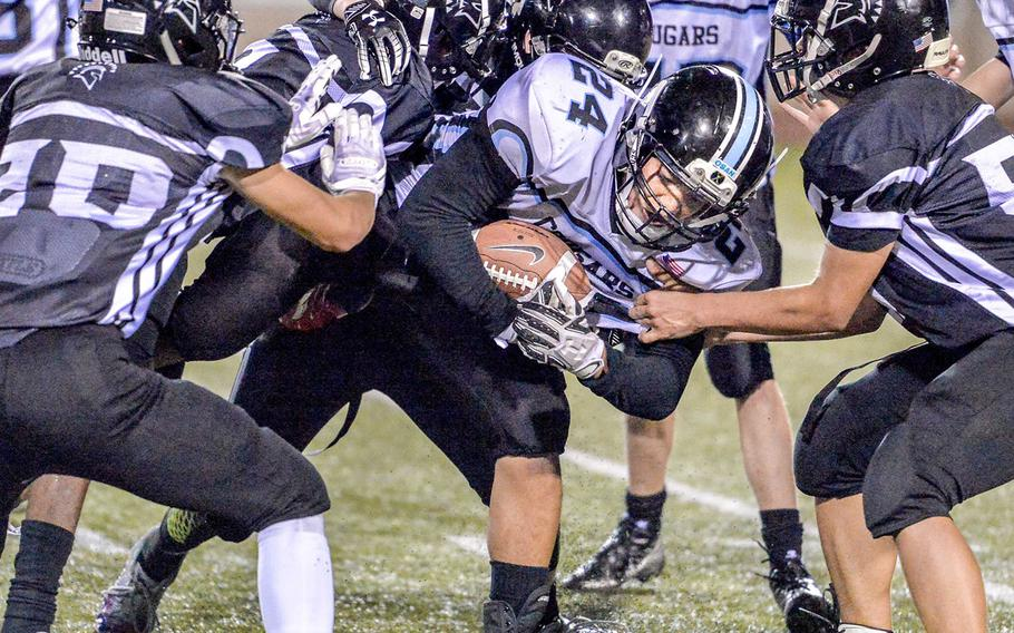 Osan's Jaden Wright fights his way through Zama defenders. He scored two touchdowns for the Cougars.