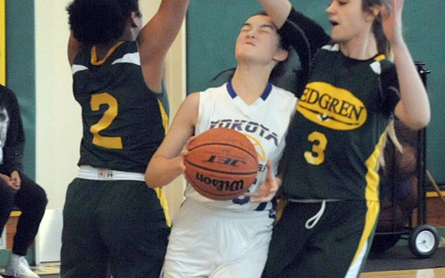 Yokota's Emily Taynton drives between two Robert D. Edgren defenders during Saturday's Japan girls basketball game, won by the Panthers 44-26.