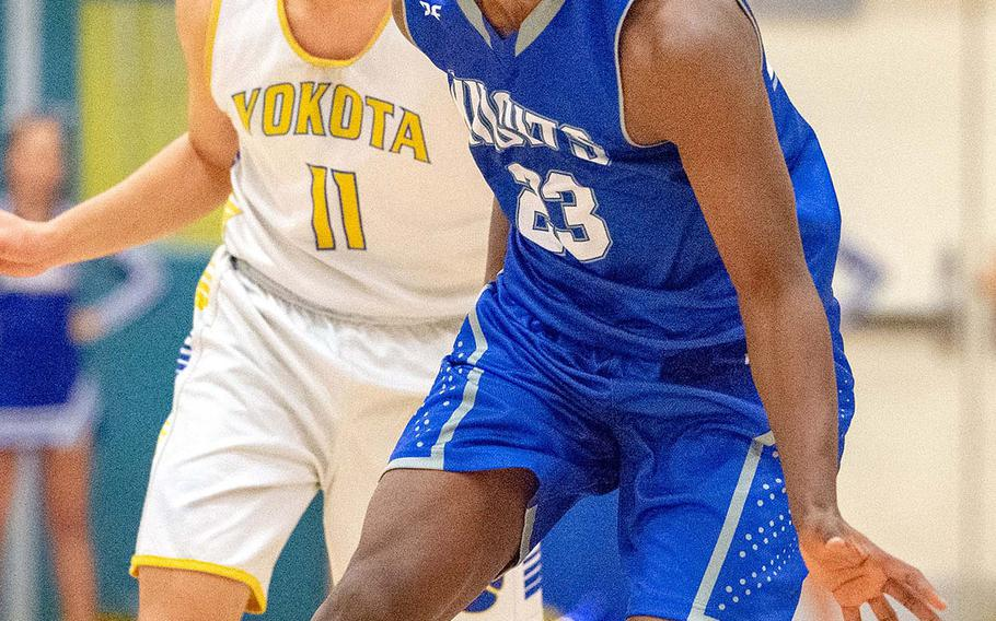 Christian Academy Japan's Enosh Mutenda dribbles ahead of Yokota's Ken Baarde during Friday's Japan boys basketball game. The Panthers won 56-44.