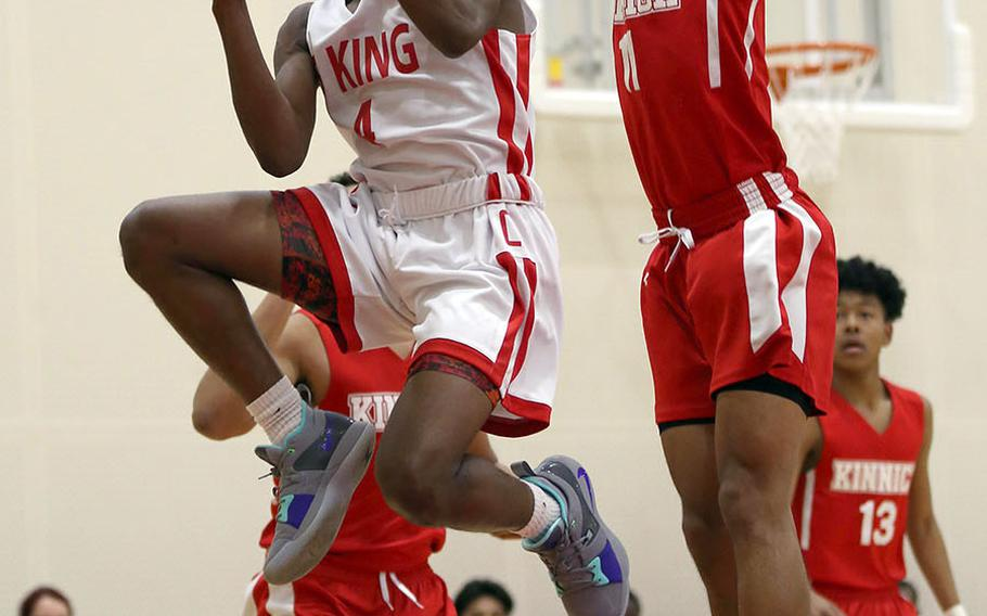 E.J. King's L.J. Scarver goes up for a shot against Nile C. Kinnick's Chris Watson during Friday's Japan boys basketball game. The Cobras won 67-62 in a battle of unbeatens.