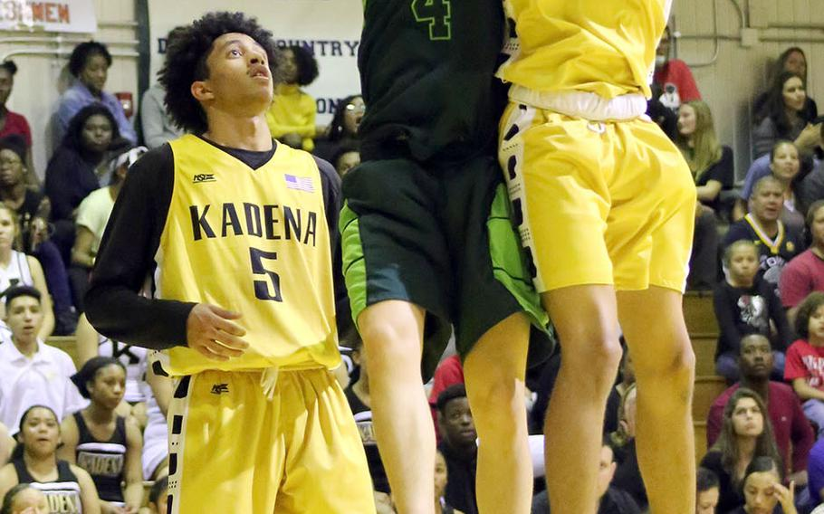 Kadena's Skyler King pulls down one of his 10 rebounds in front of Kubasaki's Mason Taylor during Friday's Okinawa boys basketball game. The Panthers won 57-48 to clinch their third straight season series and district title over the Dragons.
