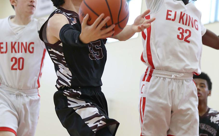 Matthew C. Perry's Gabriel Barrera tries to shoot against E.J. King's Chris Fizer during Saturday's Japan boys basketball game. The Cobras won 60-39.