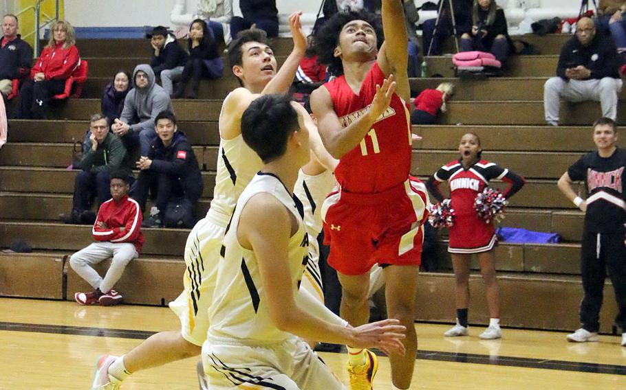 Nile C. Kinnick's Chris Watson drives for a layup against American School In Japan defenders during Saturday's rematch of last year's Far East Division I and combined tournament finals. The defending D-I champion Red Devils edged the defending combined champion Mustangs 70-62.