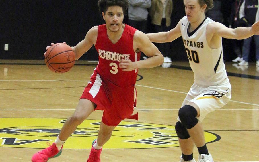 Nile C. Kinnick's Davion Roberts dribbles against American School In Japan's Adam Knode during Saturday's rematch of last year's Far East Division I and combined tournament finals. The defending D-I champion Red Devils edged the defending combined champion Mustangs 70-62.