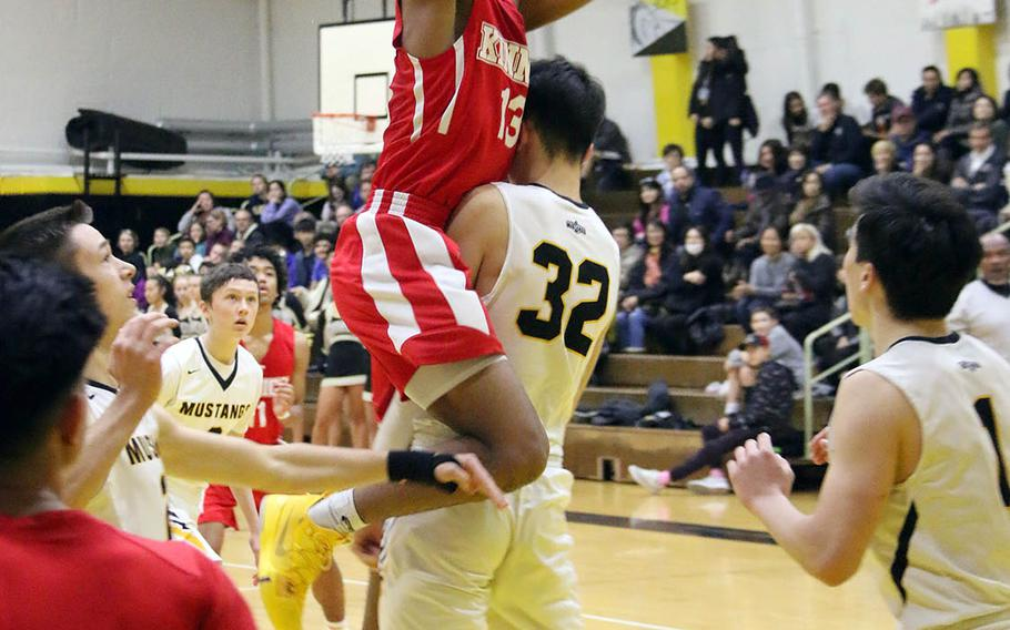 Nile C. Kinnick's Kaine Roberts shoots and plows into American School In Japan's Chris Sasanuma during Saturday's rematch of last year's Far East Division I and combined tournament finals. The defending D-I champion Red Devils edged the defending combined champion Mustangs 70-62.