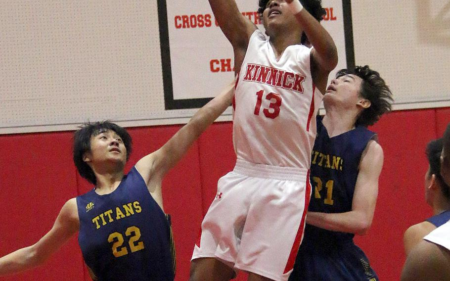 Nile C. Kinnick's Kaine Roberts shoots between St. Mary's  Lucas Wainwright and William Masuyama during Tuesday's Japan boys basketball game. The Red Devils won 51-30.