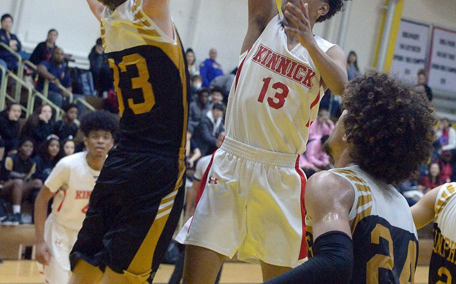 Nile C. Kinnick's Kaine Roberts shoots over Humphreys' Connor Coyne during Friday's Kanto Classic boys game. The Blackhawks won 64-56 in overtime.