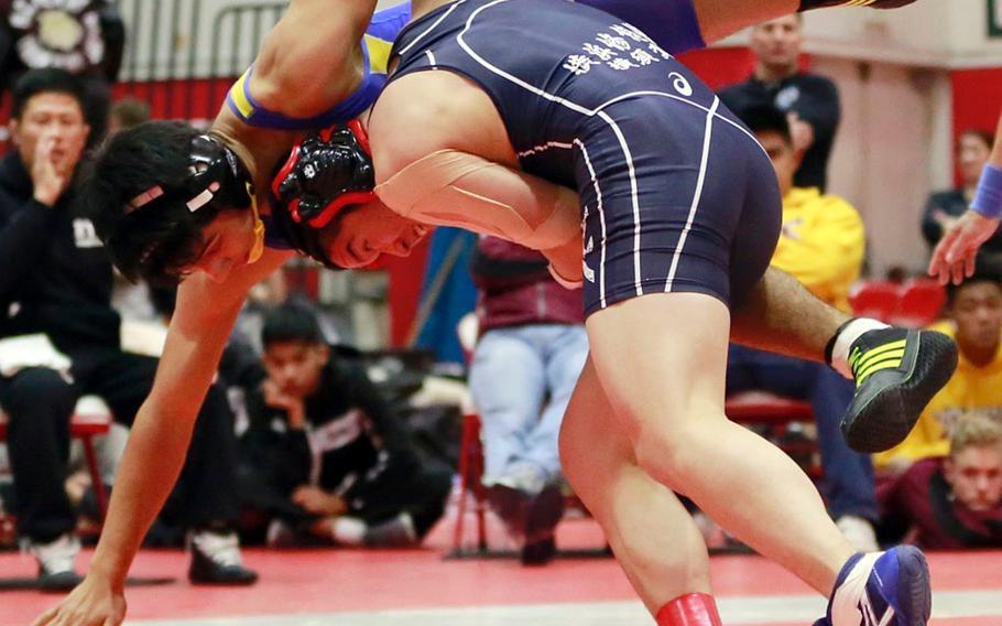 "Shonan Military Academy's Takamitsu Mineta lifts St. Mary's Warren Koslow in the 158-pound final of Saturday's Nile C. Kinnick Invitational ""Beast of the Far East"" wrestling tournament. Mineta pinned Koslow in 5 minutes, 54 seconds."