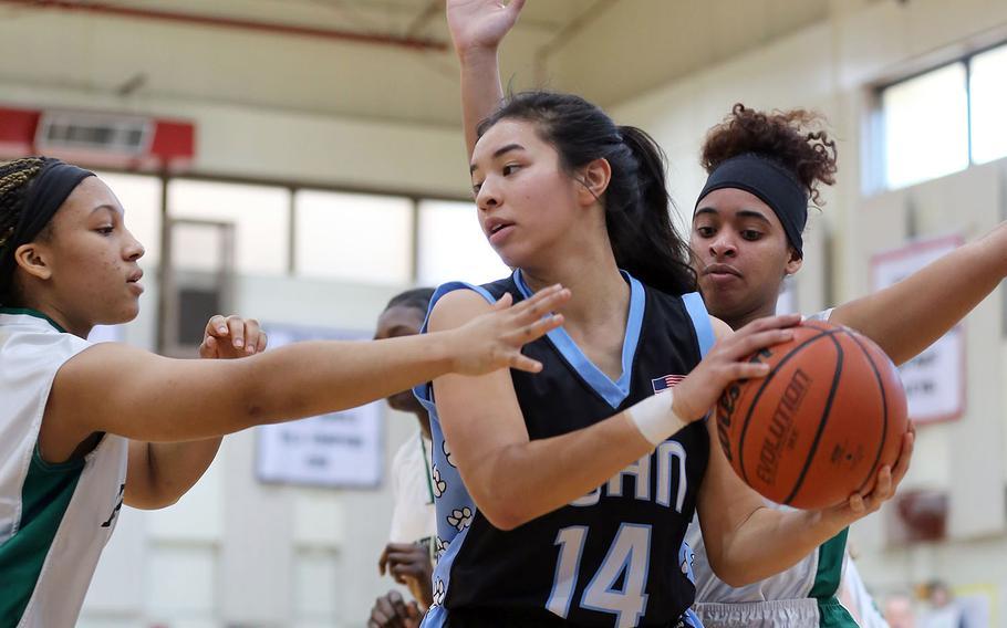 Osan American's Maja Inthavixay looks for room against Daegu's Bethani Newbold and Katrina Vasquez during Saturday's Korea girls basketball game, won by the Warriors 40-35.