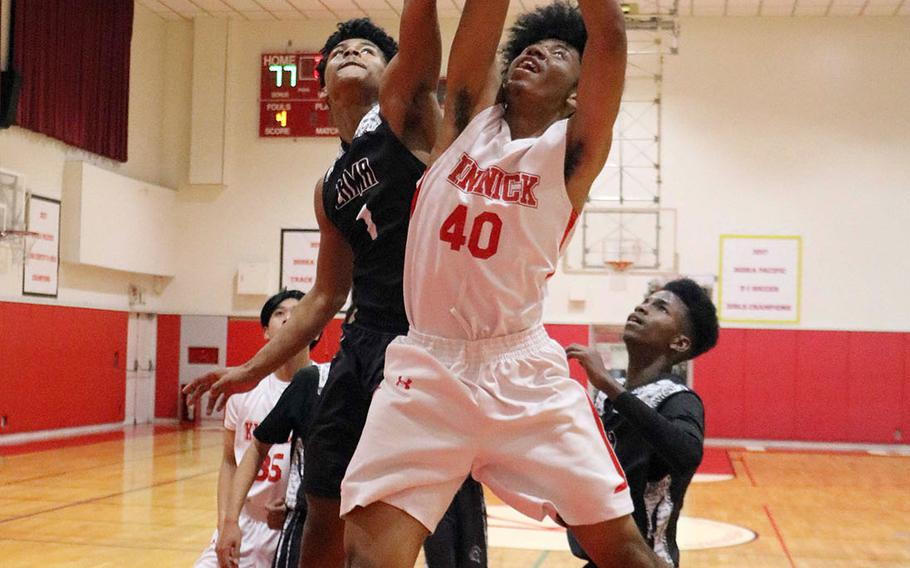 Nile C. Kinnick's Darryl Williams and Zama's Keshawn McNeil sky for a rebound during Tuesday's Japan boys basketball game. The Red Devils won 79-45.