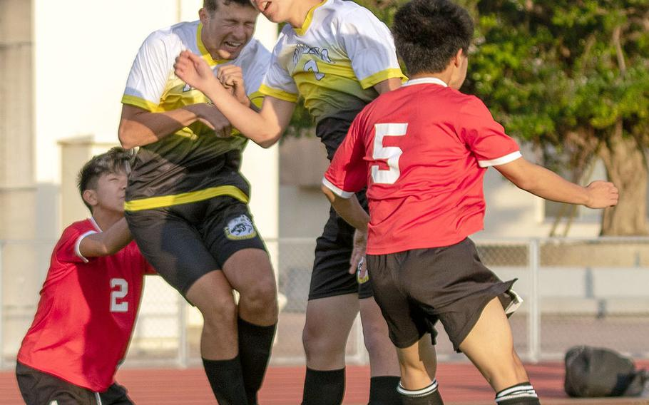 Kadena's Sean Fletcher and Nao Heckerman go up to head the ball between two Okinawa Christian defenders during Friday's Okinawa boys soccer match, won by the Panthers 4-0.