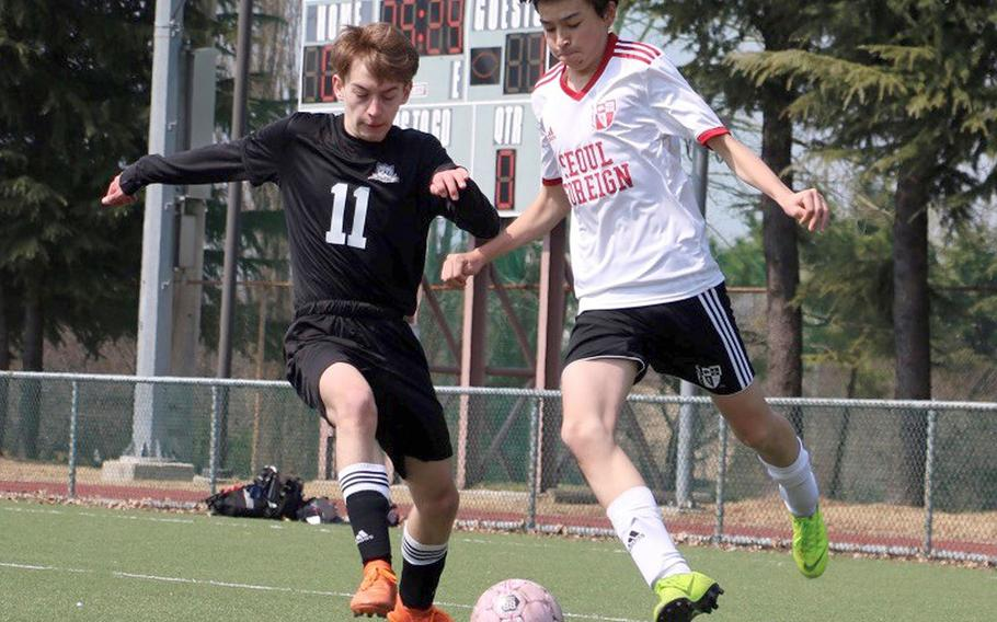 Seoul Foreign's Alex Schrader prepares to boot the ball against Daegu's Andrew Reeves during Saturday's Korea Blue boys soccer match, won by the Crusaders 4-0.
