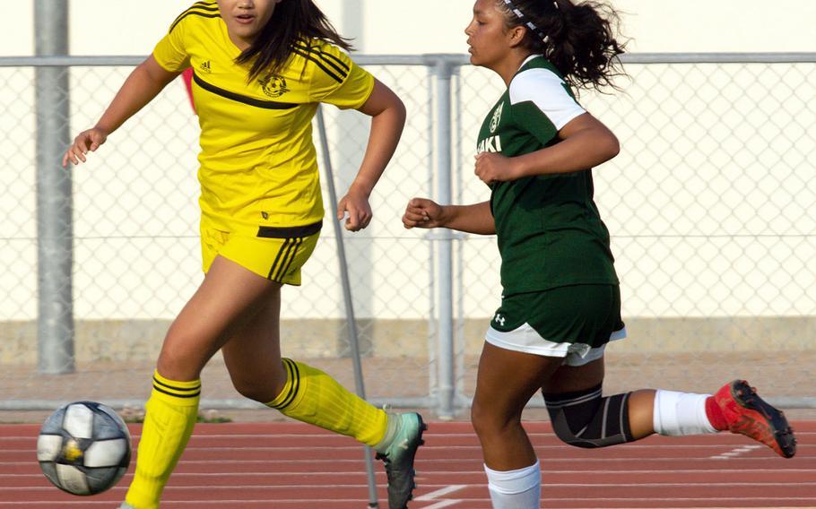 Kadena's Trinity Hannaway outruns Kubasaki's Chloe Ibarra for the ball during Wednesday's Okinawa girls soccer match, won by the Panthers 7-1.