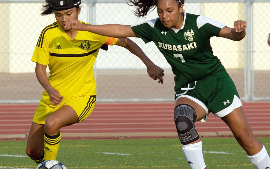 Kadena's Korina Radel and Kubasaki's Chloe Ibarra jostle for the ball during Wednesday's Okinawa girls soccer match, won by the Panthers 7-1.