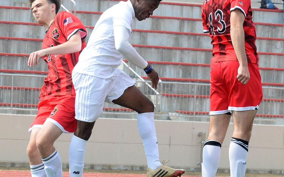 Kubasaki's Sam Gbatu heads the ball between Nile C. Kinnick's Alex Scheidt and Connor McAllister during Friday's Perry Cup match at Marine Corps Air Station Iwakuni, Japan. The Red Devils edged the Dragons 2-1. Both teams went on to reach Saturday's semifinals.