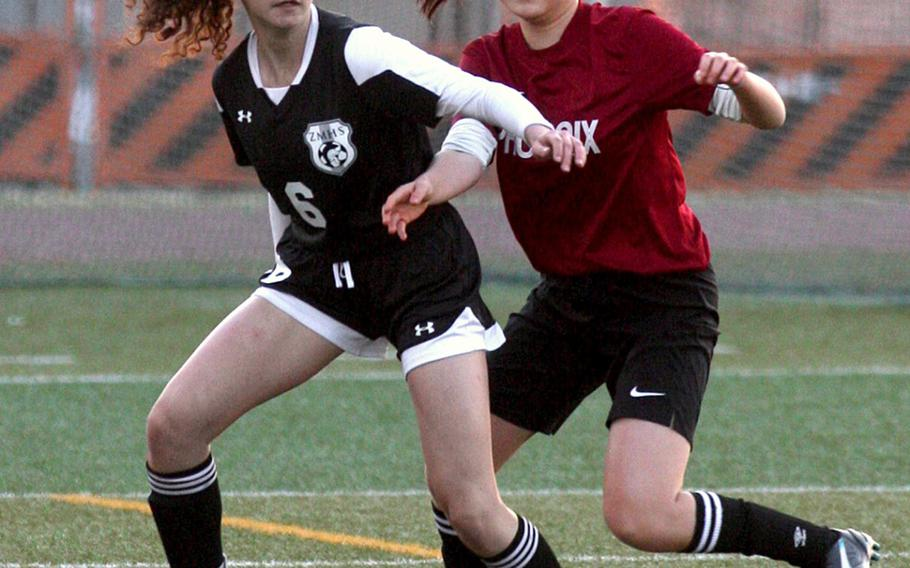 Zama's Meridean Duarte shields the ball against Seisen's Yeji Son during Wednesday's Japan girls soccer match, won by the Trojans 9-0.