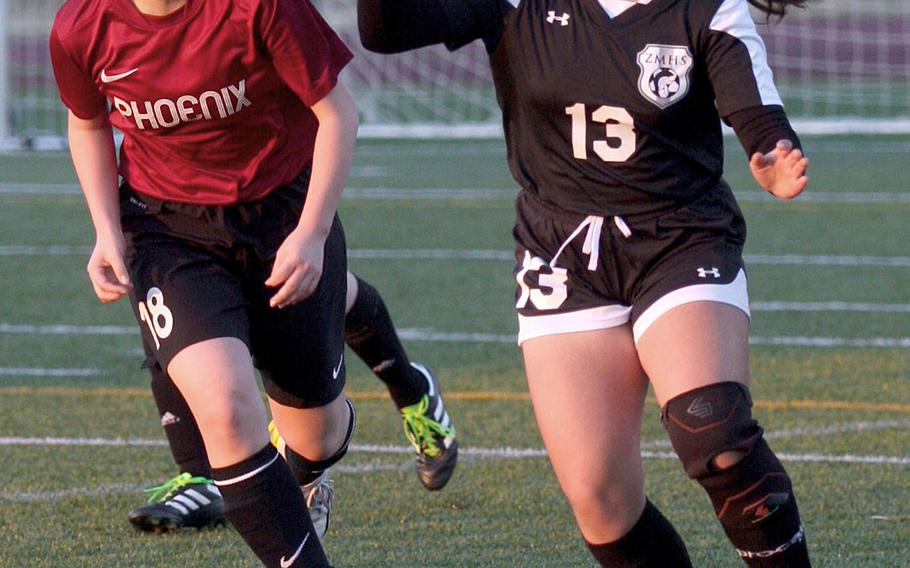 Seisen's Lina Saechout and Zama's Danielle Flores chase the ball during Wednesday's Japan girls soccer match, won by the Trojans 9-0.
