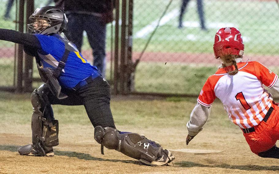 Yokota catcher Becca Bauman snags the throw as Nile C. Kinnick baserunner Faith Sells slides for home plate during Tuesday's Japan softball game. The Red Devils won 17-9, ending the Panthers' eight-game winning streak.