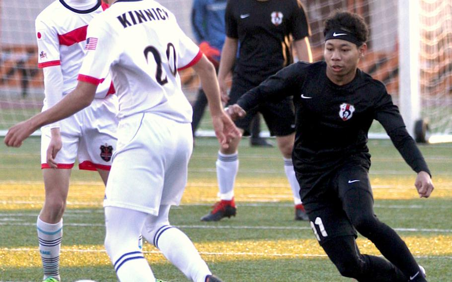 Nile C. Kinnick's Daniel Burke gets chased down by Zama's Justyn Seraphin during Tuesday's Japan boys soccer match, won by the Red Devils 7-0.