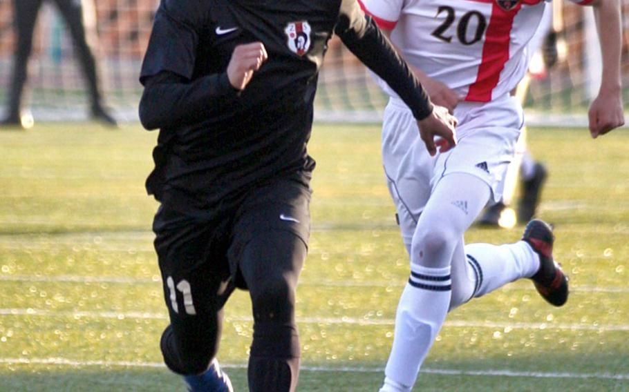 Zaman's Justyn Seraphin and Nile C. Kinnick's Daniel Burke chase the ball during Tuesday's Japan boys soccer match, won by the Red Devils 7-0.