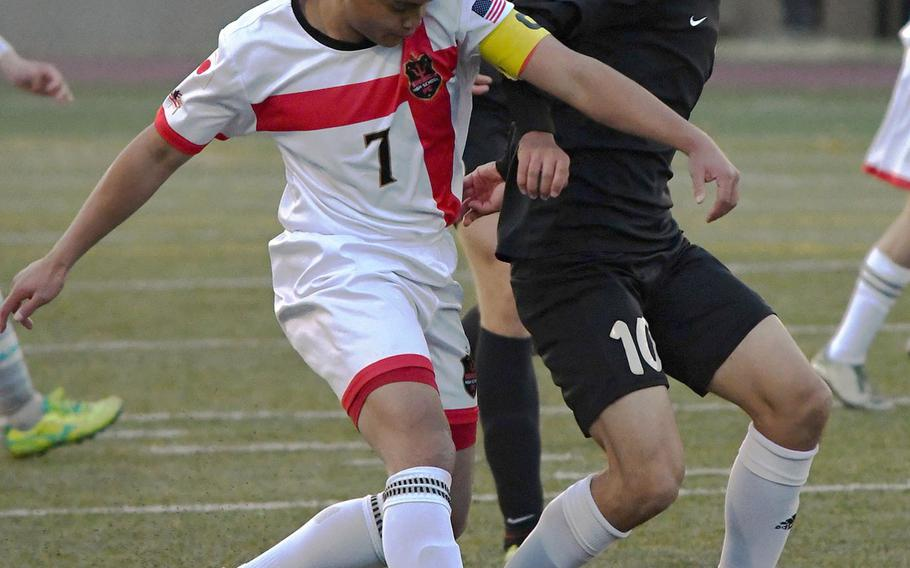 Nile C. Kinnick's Jazel Mendoza and Zama's Kai Sakata scrum for the ball during Tuesday's Japan boys soccer match, won by the Red Devils 7-0.