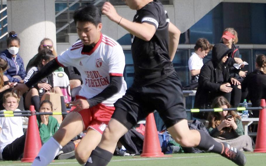Daegu's Miciiah Ruff and Seoul Foreign's Daniel Kim chase the ball during Friday's Korea boys soccer match, won by the Crusaders 5-0.