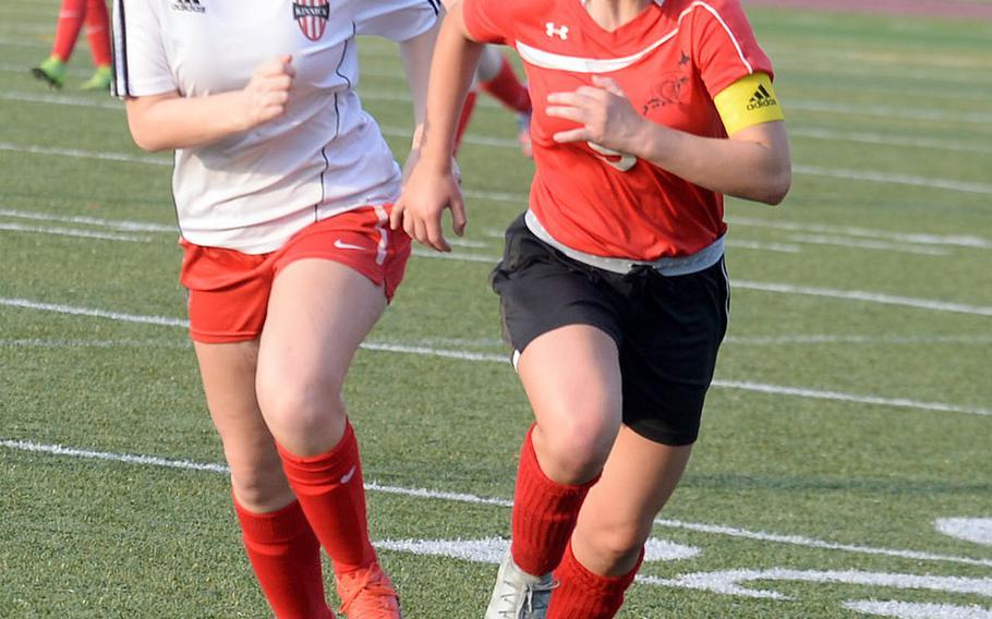 E.J. King's Gabi Shultz and Nile C. Kinnick's Jillian Mock chase the ball during Thursday's DODEA-Japan girls soccer tournament match, won by the Red Devils 4-0.