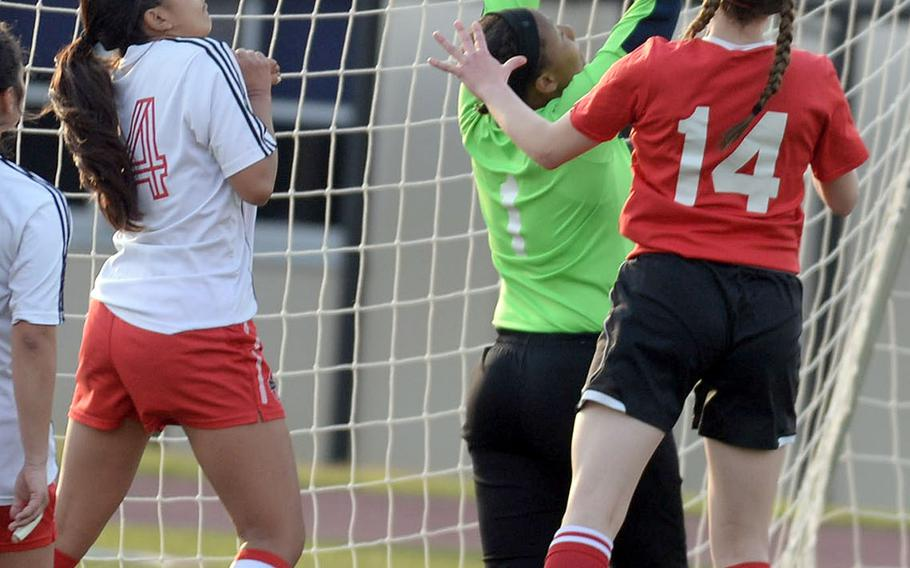 Nile C. Kinnick keeper A'Anna Taylor reaches up to field a corner kick between E.J. King's Mikayla Argyle and Red Devils teammate Maryanna Castro during Thursday's DODEA-Japan girls soccer tournament match, won by the Red Devils 4-0.