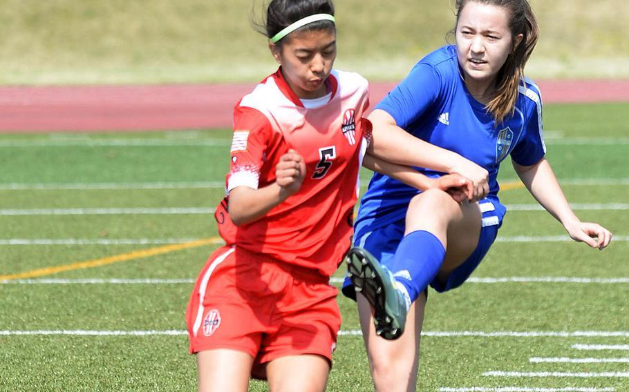 Yokota's Abby Schneider boots the ball past Nile C. Kinnick's Sakura Lopez during Thursday's DODEA-Japan girls soccer tournament match, won by the Red Devils 1-0.