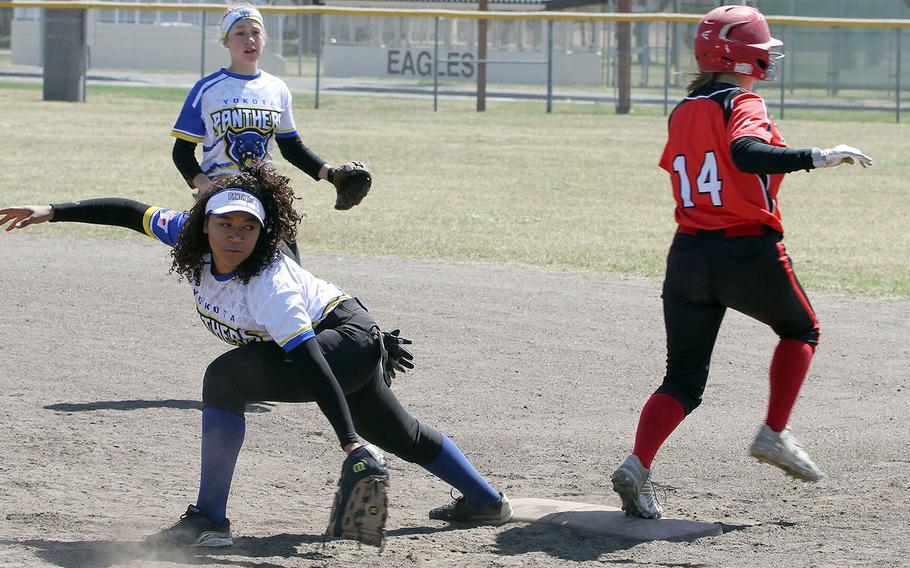 Nile C. Kinnick baserunner Rebecca Loffreda is safe at first as Yokota first baseman Isabella Mollison looks back for the ball during Saturday's DODEA-Japan softball tournament final. The Panthers won 11-9.