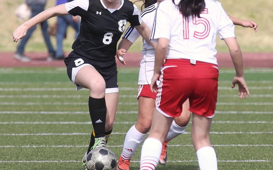 Zama's Siobhan Grabski sizes up a run between two Nile C. Kinnick defenders during Saturday's DODEA-Japan girls soccer tournament final. The Red Devils won 4-0.