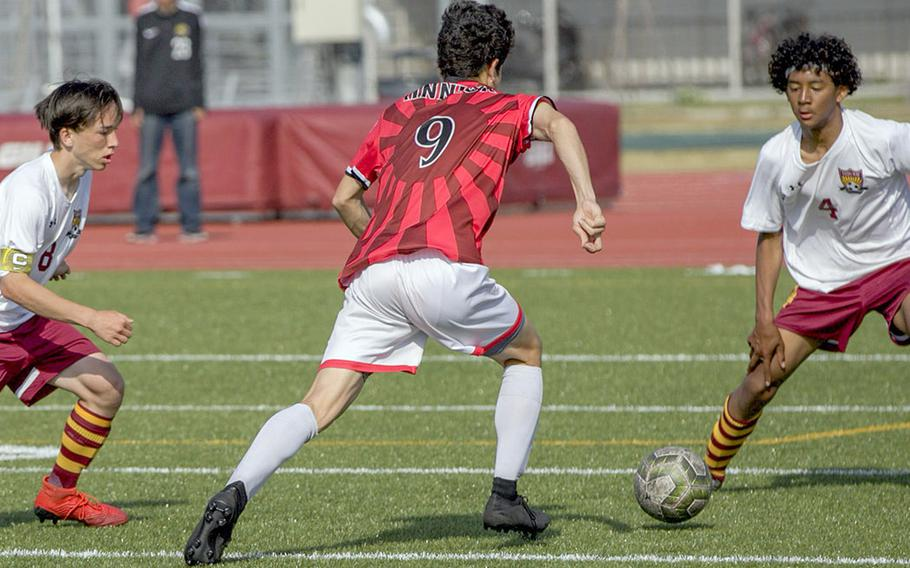 Nile C. Kinnick's Kai Sullivan looks to weave between Matthew C. Perry defenders Brad Ponsiano and Shion Fleming during Saturday's DODEA-Japan boys soccer tournament final. The Samurai won 4-1.