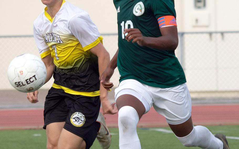 Kadena's Logan Taylor and Kubasaki's Jeffrey Horton chase the ball during Wednesday's Okinawa boys soccer match. The teams battled to a 2-2 draw.