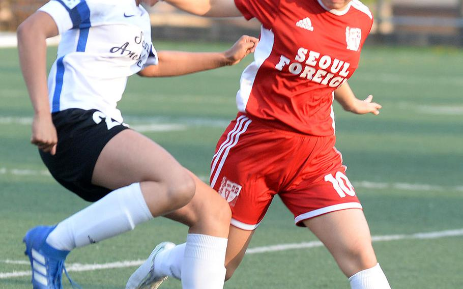 Seoul American's Mya Rolison and Seoul Foreign's Rachel Kahng battle for the ball during Wednesday's Korea girls soccer match. The Crusaders won 4-1 and clinched the Korea Blue regular-season championship.