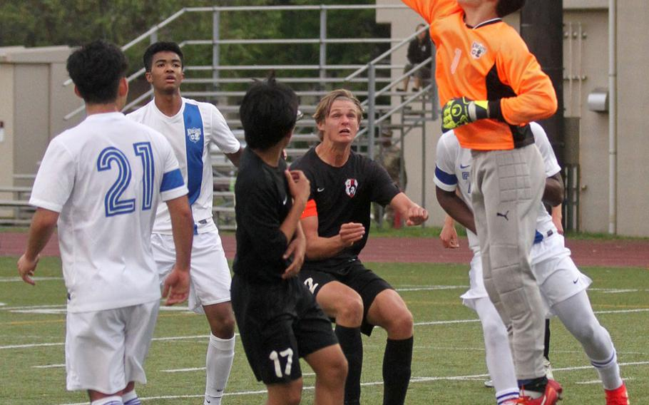 Christian Academy Japan goalkeeper Ken Byrd slaps the ball away from Zama's Kaito Hayashi and Isaac Norton during Wednesday's Japan boys soccer match. The Knights won 9-0.