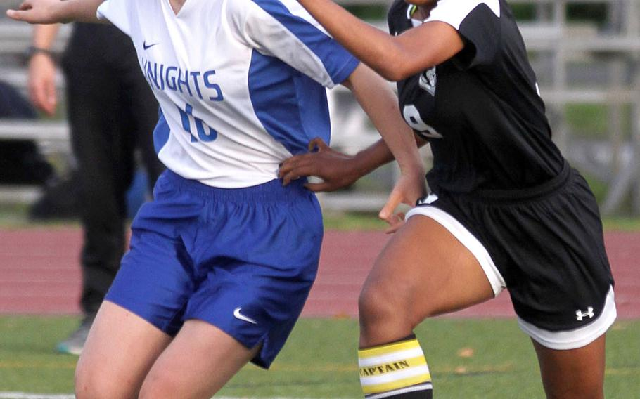 Christian Academy Japan's Maika Edberg and Zama's Kayesha McNeill chase the ball during Tuesday's Japan girls soccer match, won by the Trojans 6-1.