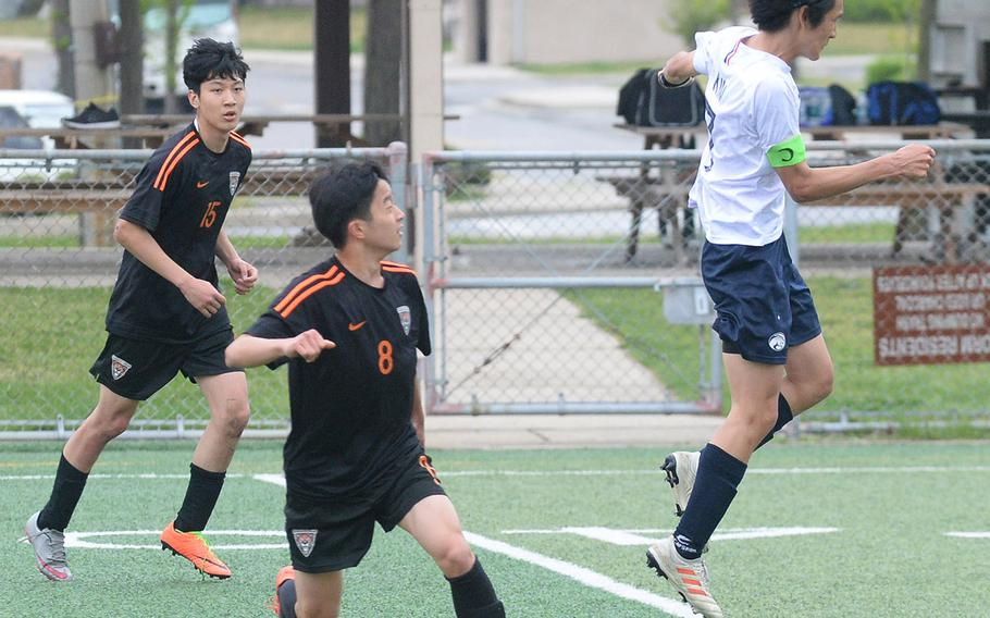 Osan's Minsung Kim heads the ball in front of Seoul International's Eddie Hahm and Archie Lee during Friday's Korea boys soccer Plate Tournament at Osan Air Base. The host Cougars won 3-0.